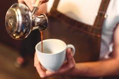 咖啡馆倾吐的咖啡的职员到杯子里 免版税图库摄影