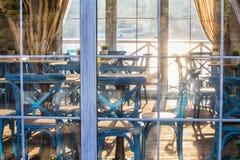 咖啡馆内部在玻璃门面后的在日落 免版税库存照片