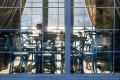 咖啡馆内部在玻璃门面后的在日落 免版税库存图片
