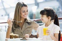 咖啡馆吃母亲的蛋糕女儿 免版税库存图片