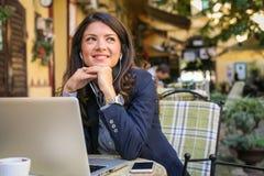 咖啡馆听的音乐的微笑的少妇,使用技术 库存照片
