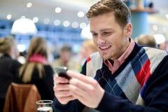 咖啡馆和使用的他的手机年轻人 免版税图库摄影