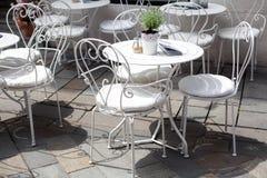 咖啡馆和桌室外大阳台与美丽的白色锻铁椅子的在晴朗的夏日 免版税库存图片