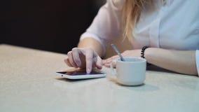咖啡馆城市电话饮用的咖啡短信的正文消息的生活方式妇女在智能手机app坐室内在时髦都市 库存图片
