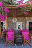 咖啡馆大阳台在Kamari,圣托里尼,有桃红色椅子和木p的 免版税库存图片