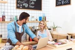 咖啡馆所有者愉快的年轻夫妇使用膝上型计算机和微笑的其中每一 库存图片