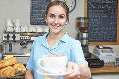 咖啡馆服务顾客的女服务员用咖啡 免版税库存图片