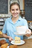 咖啡馆服务顾客的女服务员用咖啡 库存照片