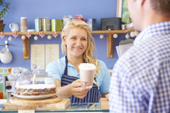 咖啡馆服务顾客的女服务员用咖啡 免版税库存照片