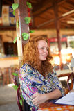 咖啡馆的一个卷曲红头发人女孩 库存照片