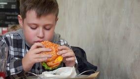 咖啡馆的一个少年吃汉堡包的 他是饥饿,鲜美和水多的汉堡包 股票录像