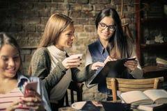 咖啡馆的三个学生女孩 免版税库存照片