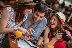 咖啡馆的三个年轻游人 库存照片