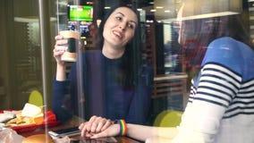 咖啡馆的两个女孩传达并且握有LGBT镯子的手 股票视频