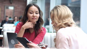 咖啡馆的两位美丽的女性使用数字式片剂 库存照片