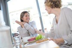 咖啡馆的两名妇女在购物以后 免版税库存照片