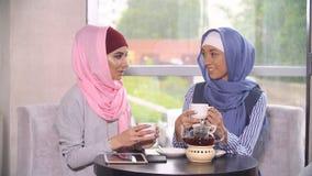 咖啡馆的两名美丽的年轻回教妇女沟通 图库摄影