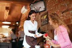 咖啡馆的人们 服务女性客户的女服务员 库存图片