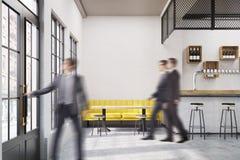 咖啡馆的人们与一个黄色沙发 免版税库存图片