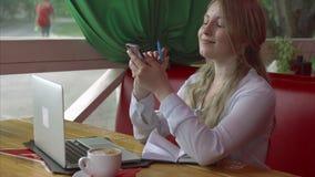 咖啡馆的女商人与智能手机膝上型计算机和笔记本一起使用 股票录像