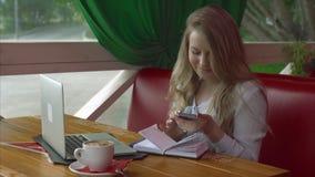 咖啡馆的女商人与智能手机膝上型计算机和笔记本一起使用 影视素材
