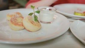 咖啡馆的女孩吃与酸性稀奶油叉子和刀子的乳酪薄煎饼 影视素材