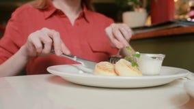 咖啡馆的女孩吃与酸性稀奶油叉子和刀子的乳酪薄煎饼 股票视频