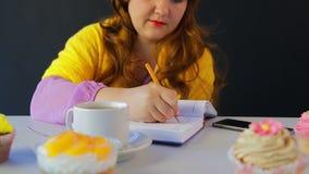 咖啡馆的女孩在桌上在日志写 股票录像