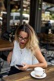 咖啡馆的女性检查她的手机的 库存图片