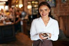 咖啡馆的女服务员 妇女用在糖果店的巧克力糖 免版税库存照片