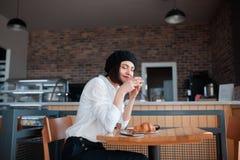 咖啡馆的妇女享用咖啡和新月形面包的 免版税库存图片