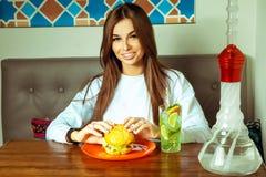 咖啡馆的妇女吃汉堡包的 免版税库存图片