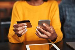 咖啡馆的妇女在网上购物与信用卡的 免版税库存照片