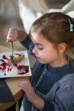 咖啡馆的小女孩吃一个点心 库存图片