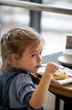 咖啡馆的小女孩吃一个点心 图库摄影