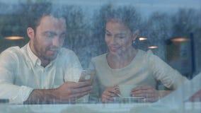 咖啡馆的少妇键入她的英俊的人的电话号码 股票录像