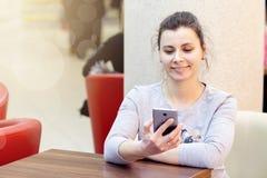 咖啡馆的年轻深色的妇女使用智能手机并且微笑 女孩在咖啡馆的wi fi Wi-Fi区域 图库摄影