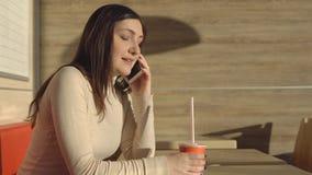 咖啡馆的年轻深色的妇女喝汁液和谈话在电话 图库摄影