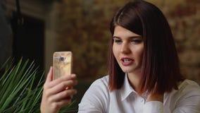 咖啡馆的微笑的女孩谈话在巧妙的电话的录影闲谈,当喝咖啡时 股票录像