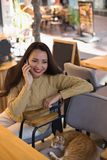 咖啡馆的微笑的女性讲话在手机 免版税库存图片