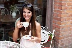 咖啡馆的微笑的年轻俏丽的女孩 免版税图库摄影