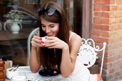咖啡馆的微笑的年轻俏丽的女孩 免版税库存图片