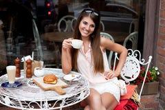咖啡馆的微笑的年轻俏丽的女孩 库存图片