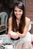 咖啡馆的微笑的年轻俏丽的女孩 免版税库存照片