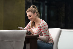 咖啡馆的愉快的女学生与触摸板 免版税库存图片