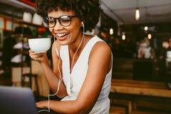 咖啡馆的愉快的妇女使用膝上型计算机 免版税库存图片