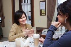 咖啡馆的成人女朋友 免版税库存照片