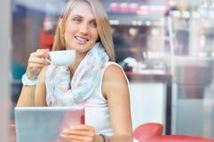 咖啡馆的时髦少妇与咖啡和触摸屏幕片剂 免版税库存照片