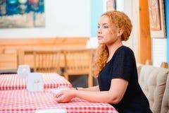 咖啡馆的美丽的妇女 免版税库存照片