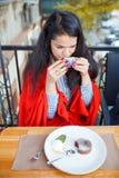 咖啡馆的美丽的深色的女孩在自然本底 免版税库存照片
